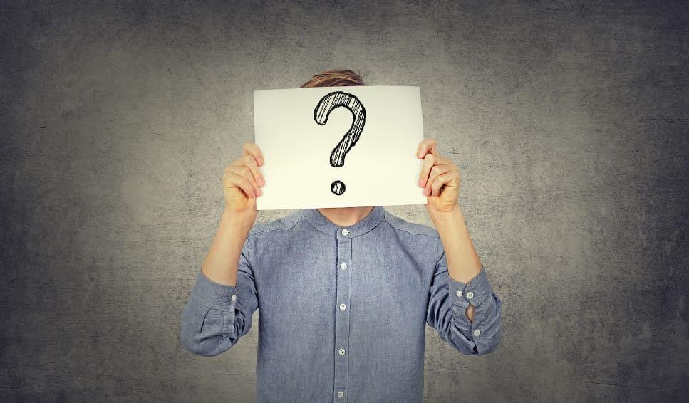 Junger Mann hält sich ein weißes Papier mit Fragezeichen vor sein Gesicht