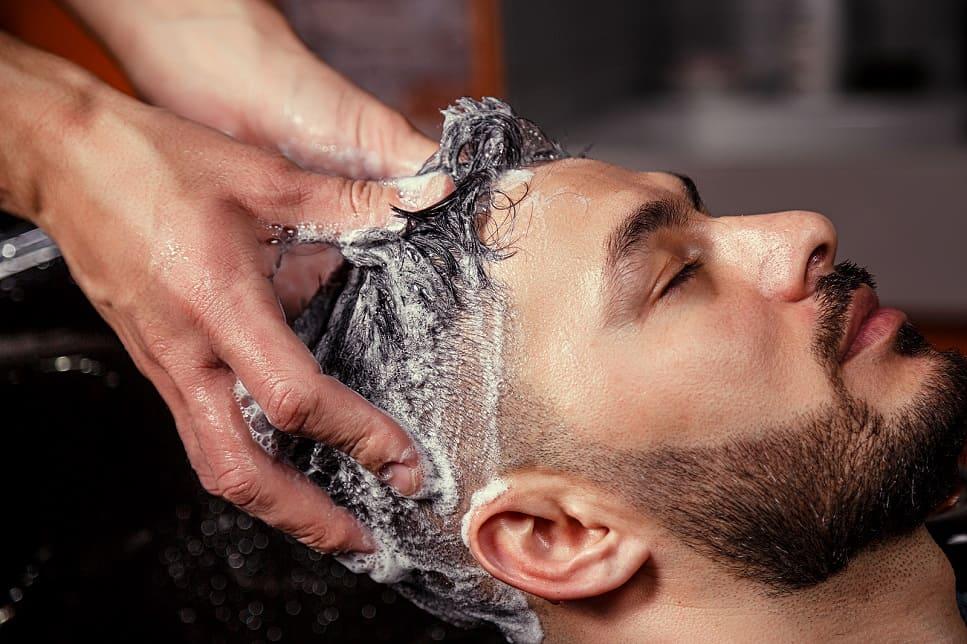 Mann bekommt beim Frisör die Haare gewaschen