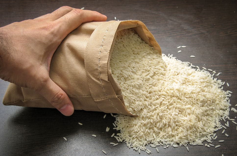Hand schüttelt Reis auf einem Tisch aus