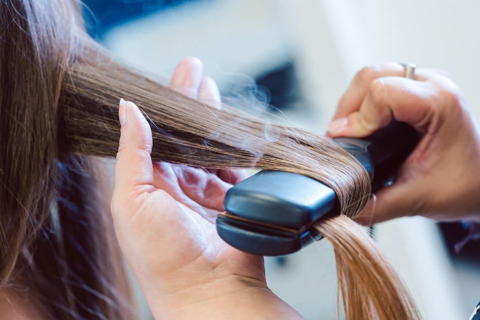 Eine Frau lässt sich die Haare glätten