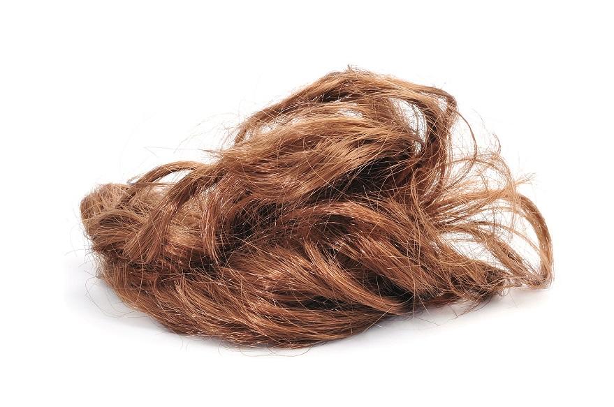 Künstliches braunes Haar auf weißem Untergrund