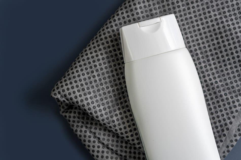 Eine weiße Shampooflasche auf einem grauen Tuch