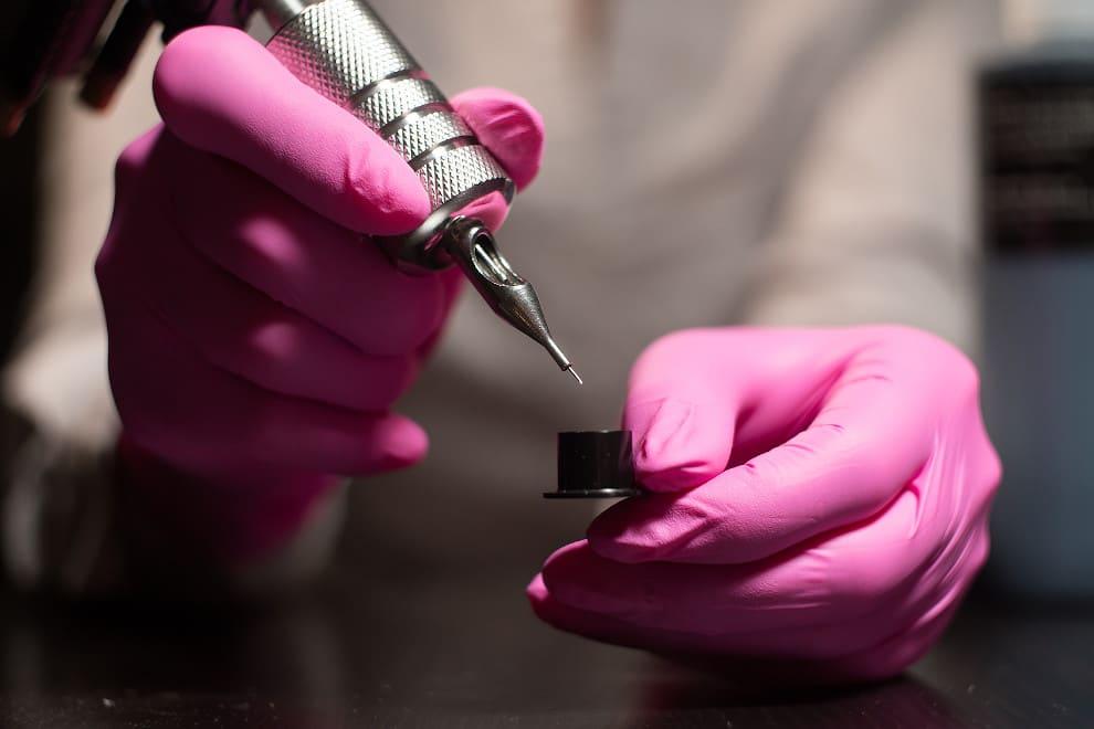 Ärztin taucht die Pigmentierungsnadel in Farbe ein