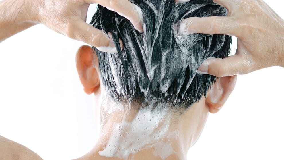 Mann wäscht sich die Haare in Rückenaufnahme