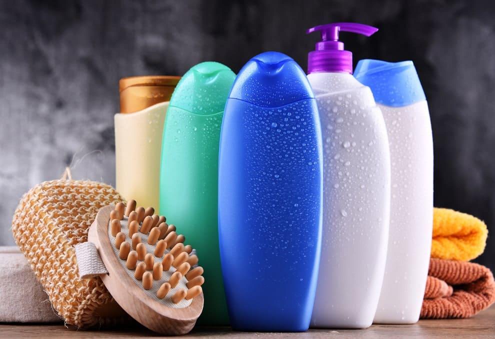 Mehrere Haarpflege Plastikflaschen neben einer Bürste und einem Schwamm vor einem grau-schwarzen Hintergrund