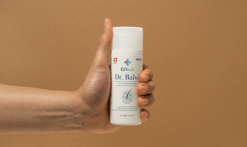Hand hält das Dr. Balwi Shampoo für pflanzliche Haarpflege vor einem beigen Hintergrund