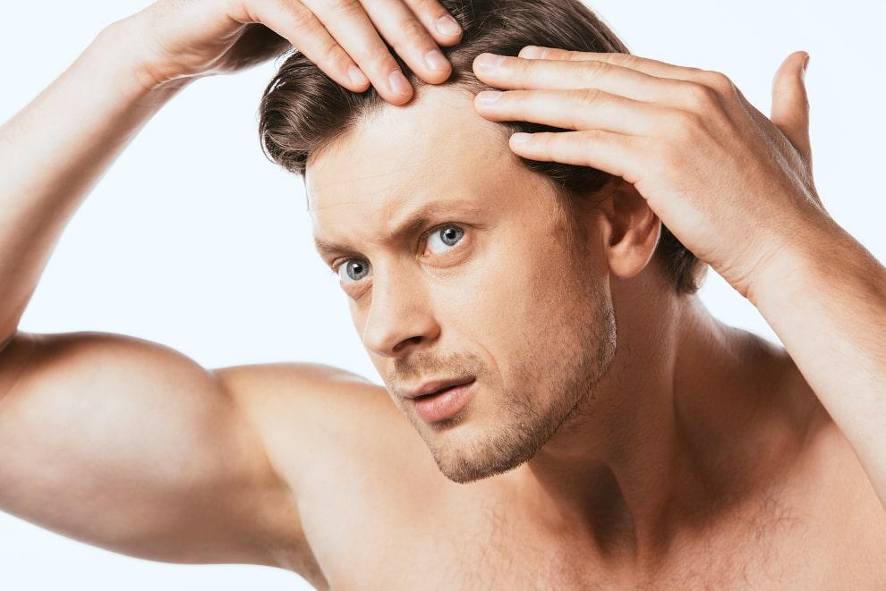 Mann steht vor einem weißen Hintergrund und begutachtet seinen Haarausfall und Geheimratsecken