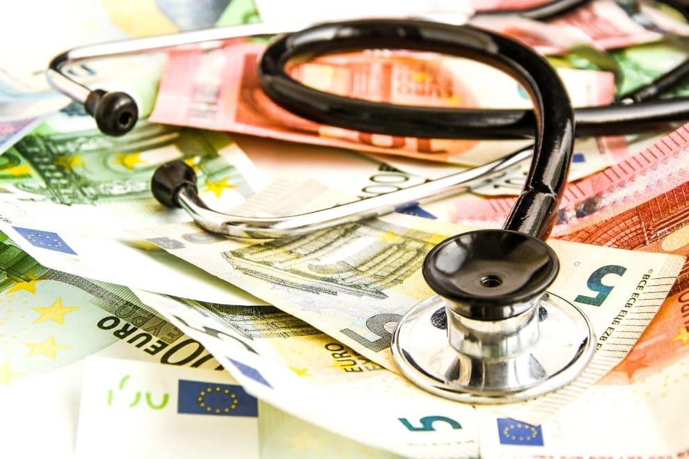 Ein Stethoskop liegt auf einem Haufen verschiedener Euro-Geldscheine