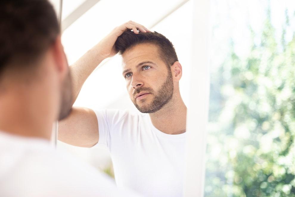 Junger Mann betrachtet seine Haarpracht im Spiegel