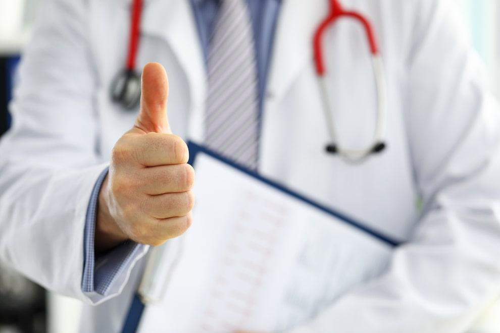 Arzt streckt den rechten Daumen in die Luft und hält eine Diagnose auf einen Schreibbrett in der linken Hand