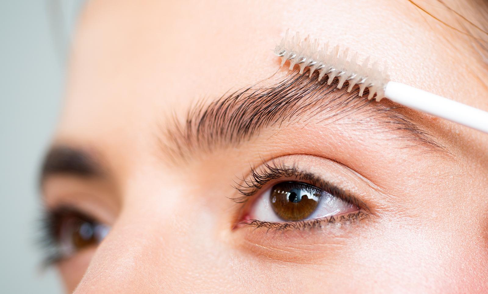 Nahaufnahme des Augenbereiches einer Frau, welche sich die Augenbrauen bürstet