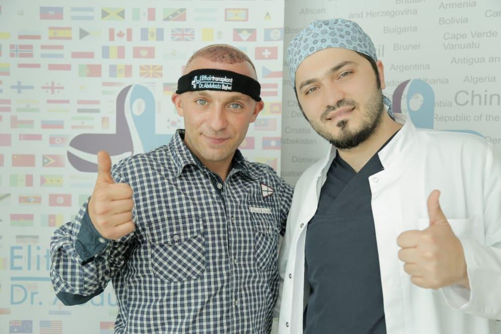 Dr.Balwi und ein zufriedener Patient nach der Haarverpflanzung stehend vor einem Elithairtransplant Banner