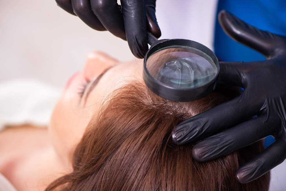 Frau liegt auf dem Rücken, während ihr Kopf mit einer Lupe untersucht wird