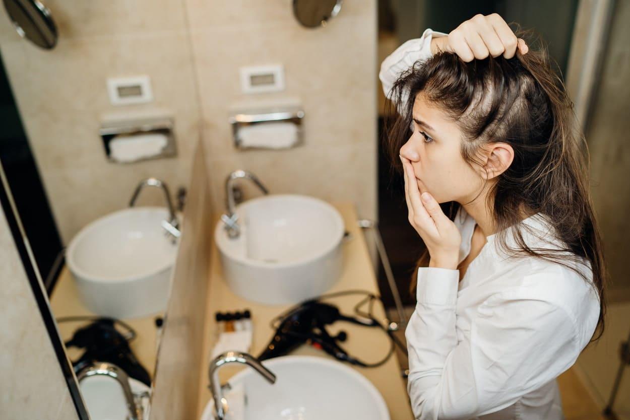 Frau guckt erschrocken in den Spiegel