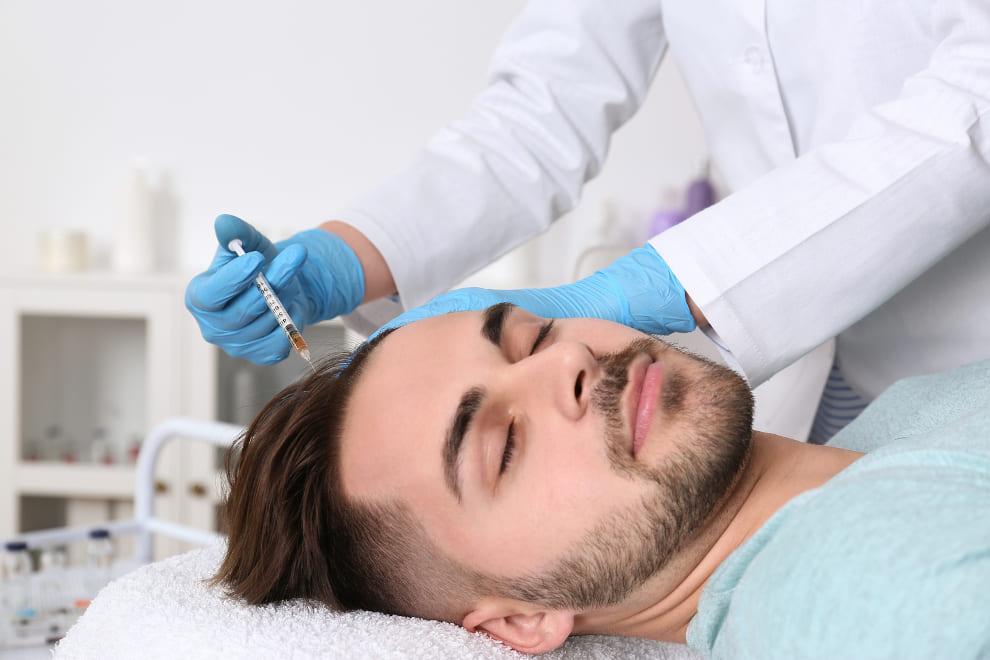 Junger Mann liegt auf dem Rücken mit geschlossenen Augen und bekommt eine PRP Behandlung
