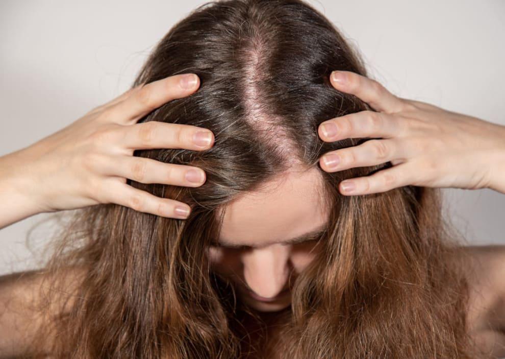 Frau mit gesenktem Kopf hält sich die Haare fest