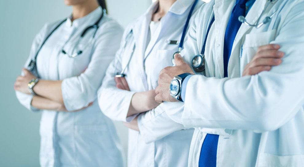 Drei Ärzte stehen mit verschrenkten Armen nebeneinander