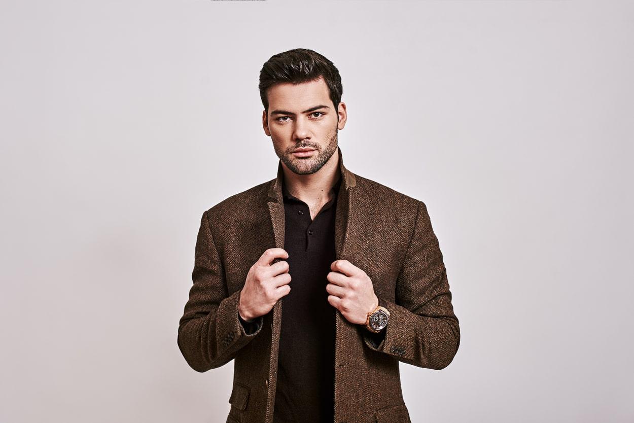 Mann steht selbstbewusst vor der Kamera und hält sich mit beiden Händen an seiner Jacke fest