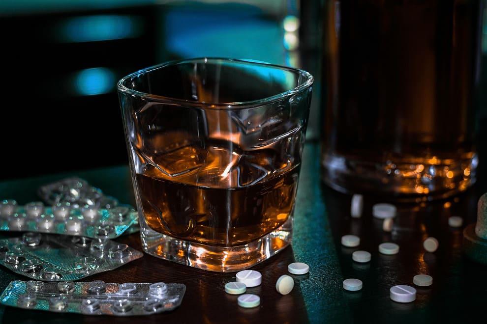 Nach der Haartransplantation: Alkohol und Medikamente auf einem schwarzen Tisch