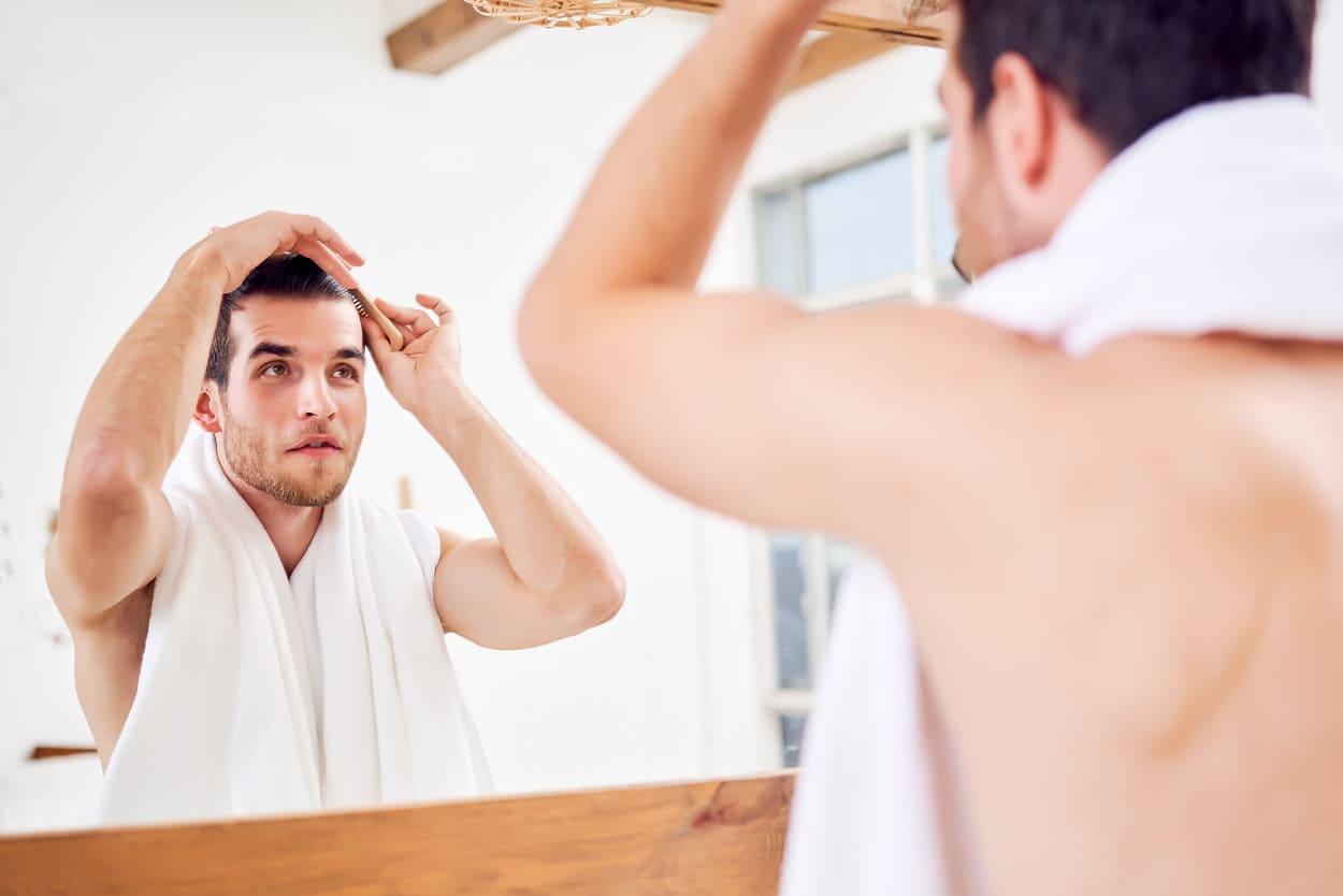 Mann kämmt sich die Haare vor einem Spiegel