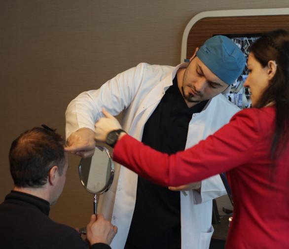 Dr Balwi analizzando i capelli pazienti prima del loro trapianto di capelli