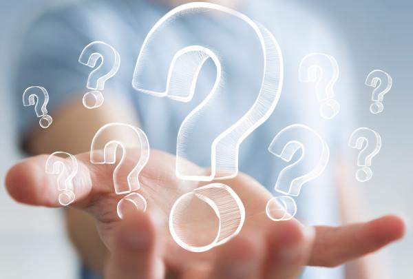 Immagine che mostra una mano aperta piena di punti interrogativi
