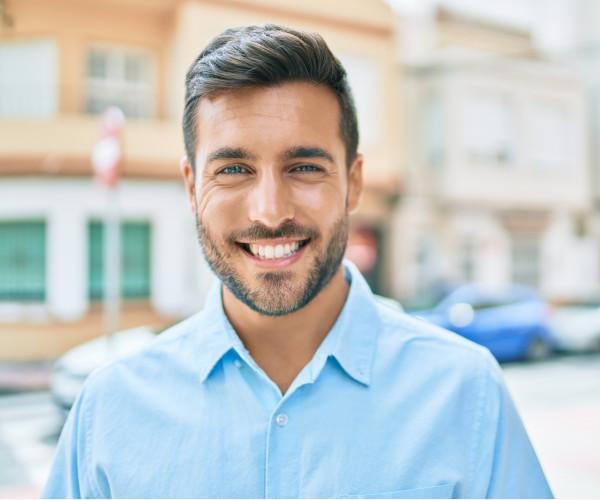 Homem sorrir depois de transplante de cabelo.