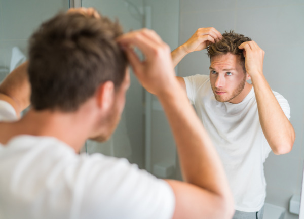 um homem olhando para o seu cabelo espesso depois de um transplante de cabelo