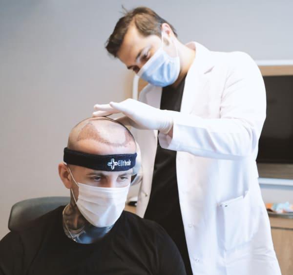 Dr. Balwi examina paciente na consulta de revisão após transplante capilar