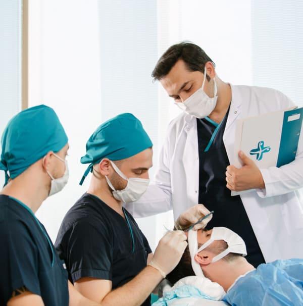 Dr. Balwi e sua equipa realizando uma intervenção de transplante capilar.
