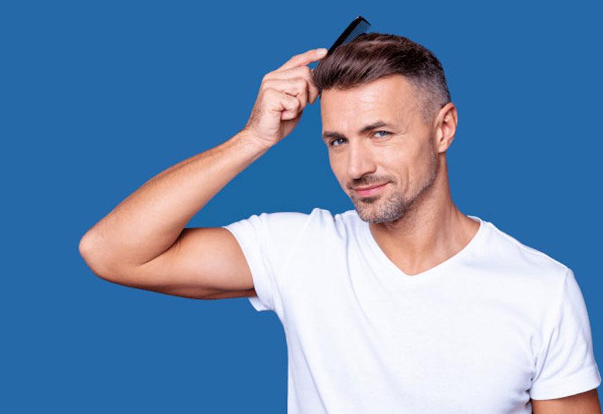 homem a ajeitar seu cabelo após transplante capilar bem sucedido