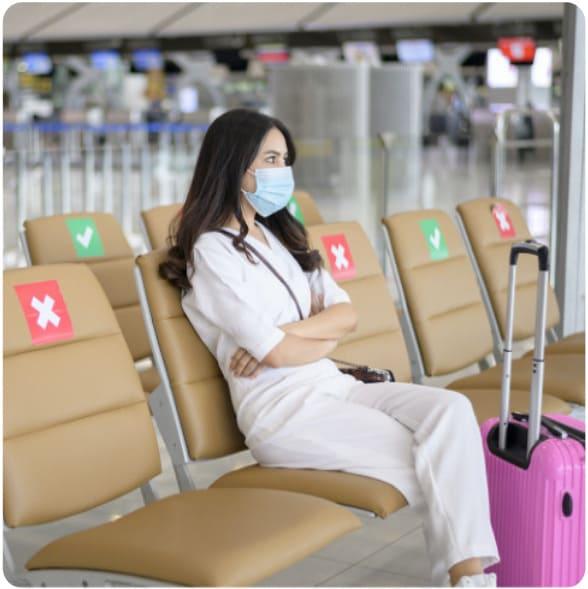 uma mulher sentada num aeroporto usando uma máscara e respeitando a distância de segurança