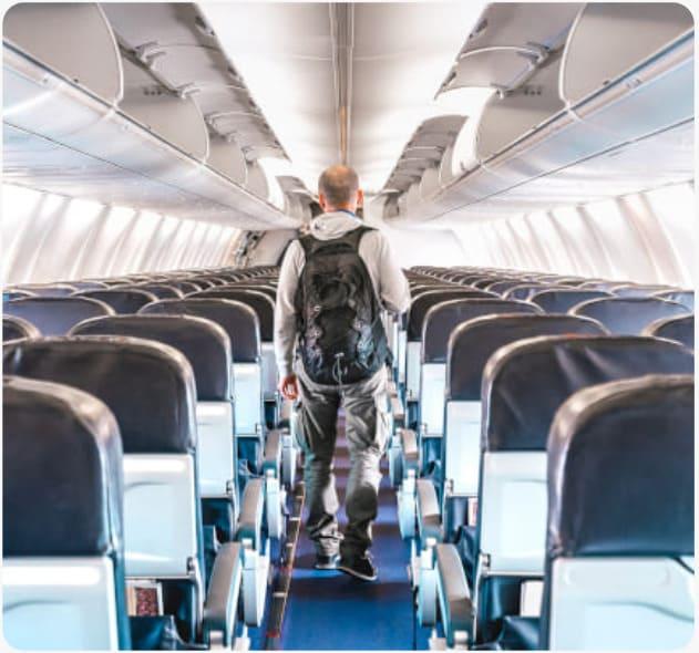um homem caminha pelo corredor do avião