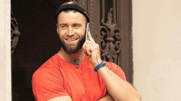 Um paciente feliz ao telefone após seu transplante de barba