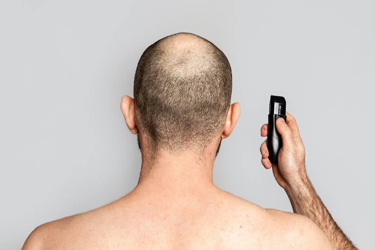 Hombre calvo sosteniendo una maguinilla de afeitar