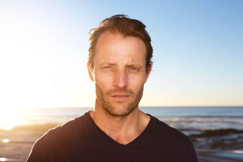 Hombre de mediana edad con pelo escaso en la playa