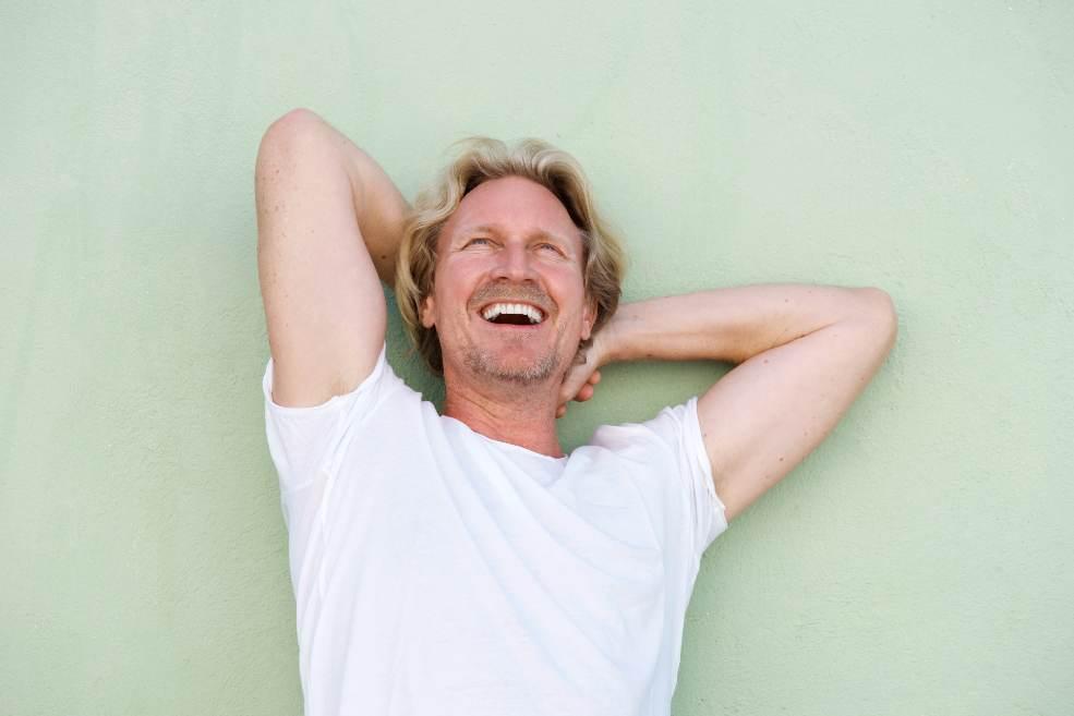 Hombre de mediana edad sonriendo con las manos tras la nuca