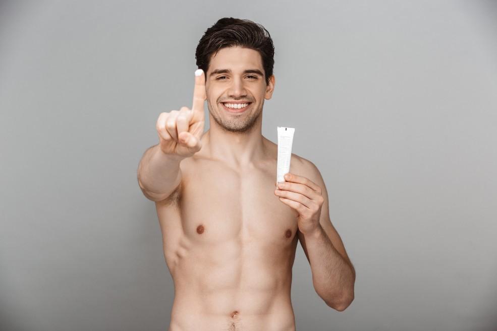 chico joven con el torso desnudo muestra en uno de sus dedos una muestra de crema mientras sonríe