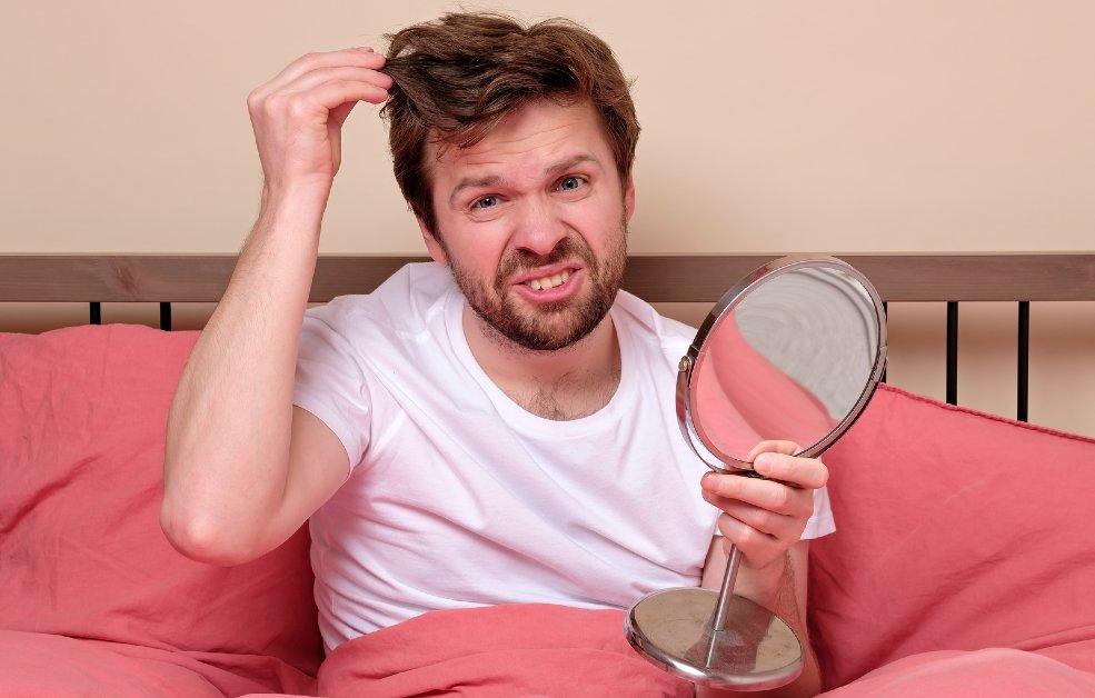 Hombre en la cama con caída de pelo
