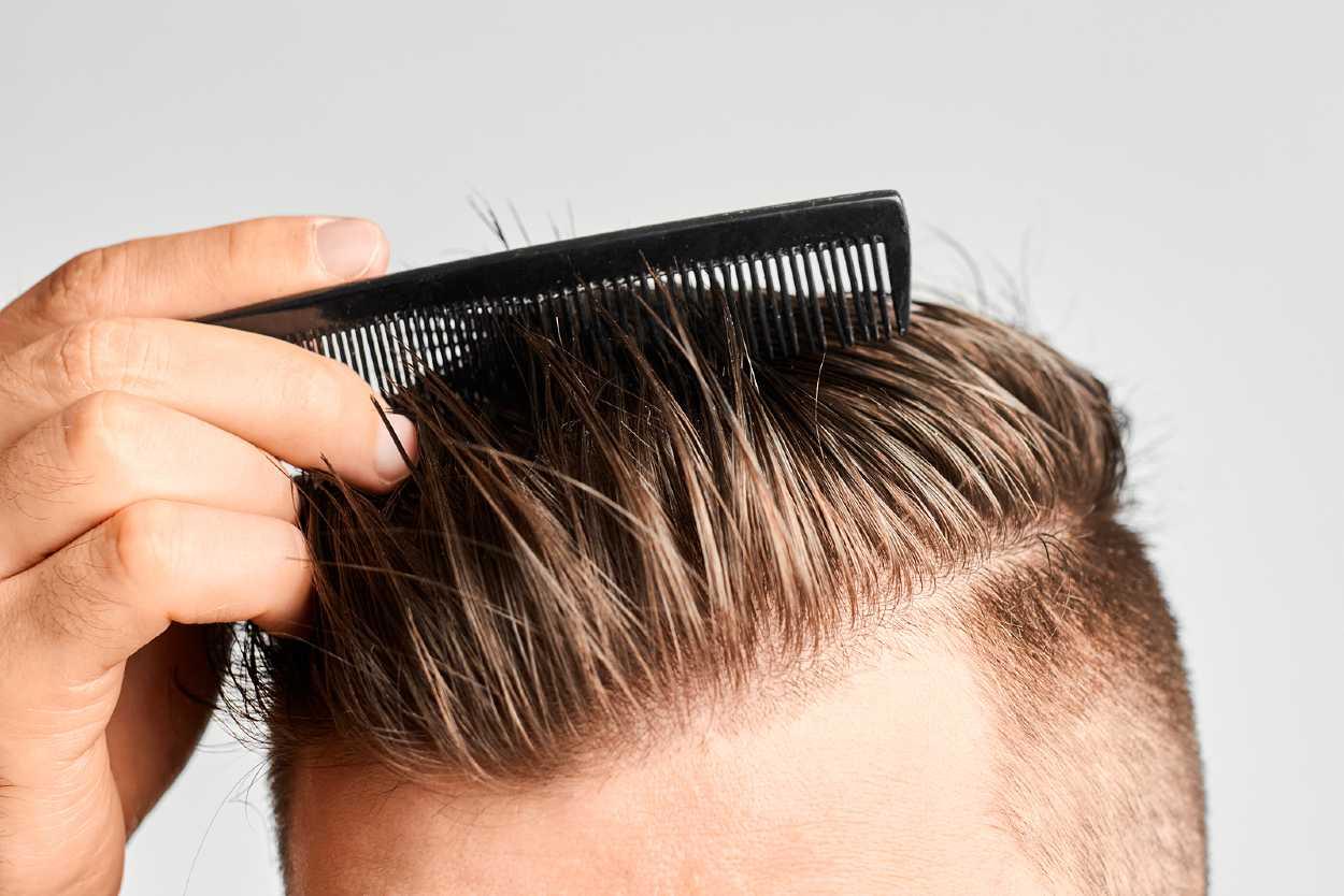 Hombre peinándose el cabello hacia el lado con un peine fino