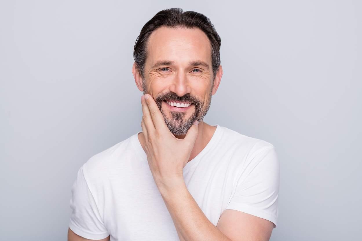 Hombre de mediana edad tocándose la barba y sonriendo