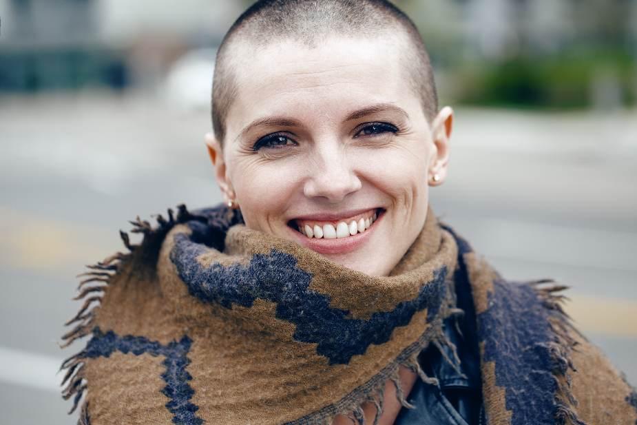 Mujer sonriente con cabeza rapada y bufanda