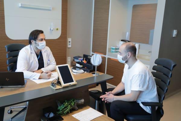 Dr. Balwi hablando con un paciente sobre el coste del injerto capilar