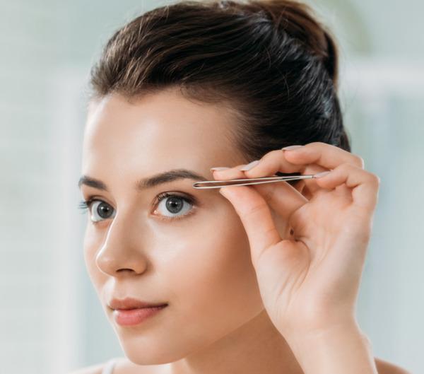 Una mujer joven se depila las cejas frente al espejo