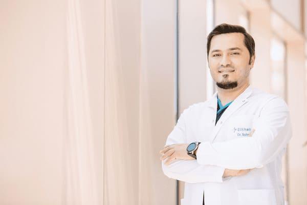 Portrait del Dr.Balwi sonriendo con los brazos cruzados y pareciendo seguro de sí mismo