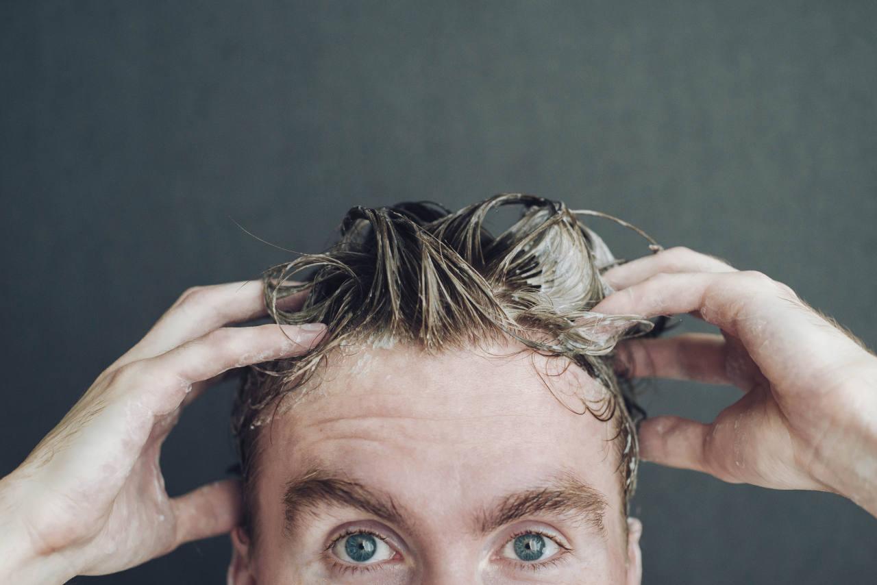 A man applying minoxidil foam to his head