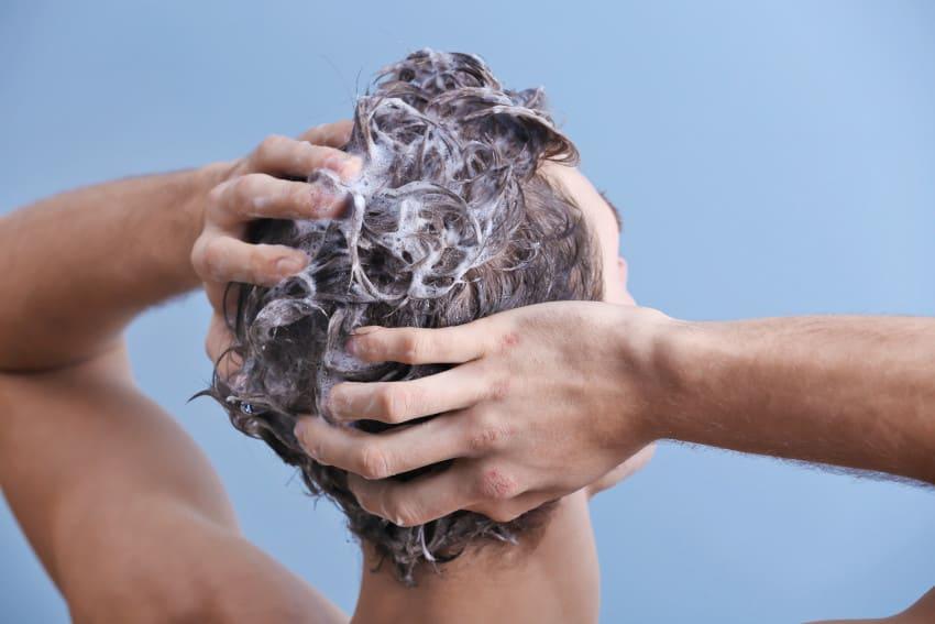 A man washing his hair with anti-hair loss shampoo